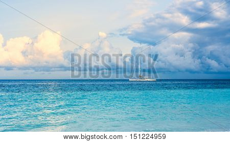 beautiful colorful seascape with sailing ship on the horizon of blue ocean and sky