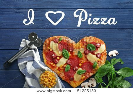 Text with tasty heart-shaped pizza and ingredients on wooden background