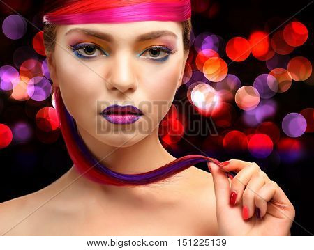 Beautiful girl with colorful makeup and hairstyle on dark shiny background