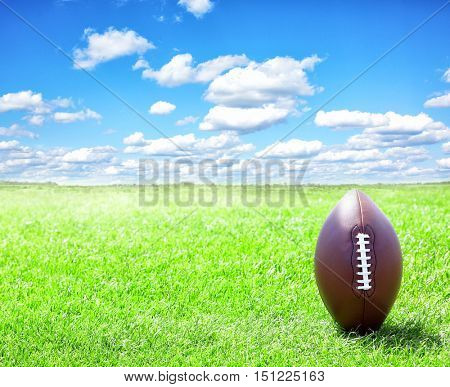 American football ball on green grass and blue sky background