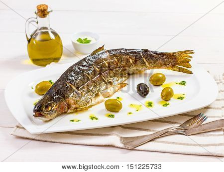 Grilled trout with olive on plate, top view