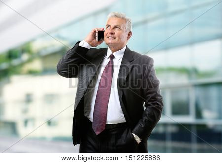Businessman talking on phone on blurred building background. Lawyer and notary concept.