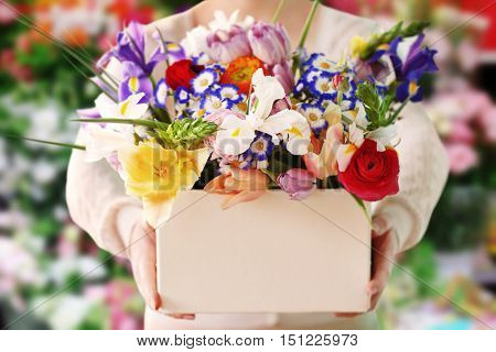 Woman holding a box of fresh flowers on flower shop background