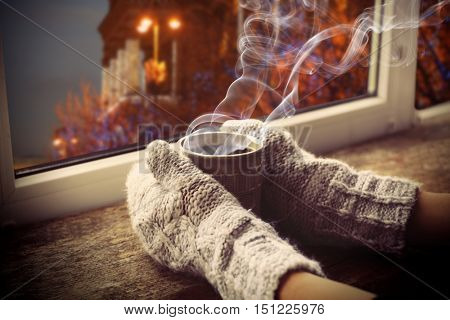 Hands in gloves with cup of hot drink on the windowsill