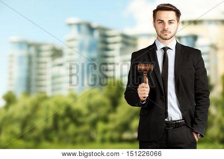 Handsome man judge gavel on blurred building background. Justice concept.