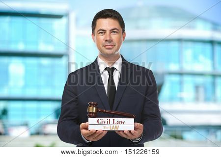 Handsome man with law books and judge gavel on blurred building background. Justice concept.