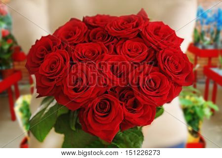 Female hands with beautiful bouquet of red roses on flower shop background