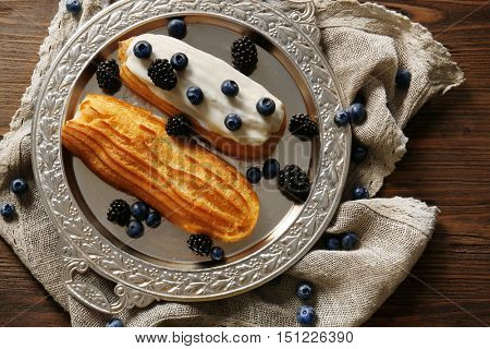 Delicious eclairs with berries in silver tray on bagging and wooden background