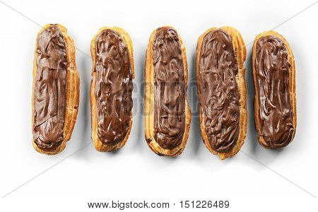 Delicious eclairs with chocolate in a row on white background