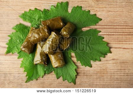 Stuffed delicious Dolma on vine leaf and wooden background