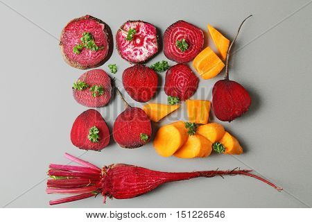 Fresh young sliced beets and carrots with parsley on grey background