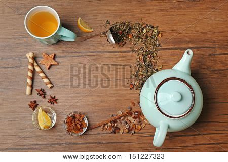 Ingredients for tea drinking on wooden background, flat lay