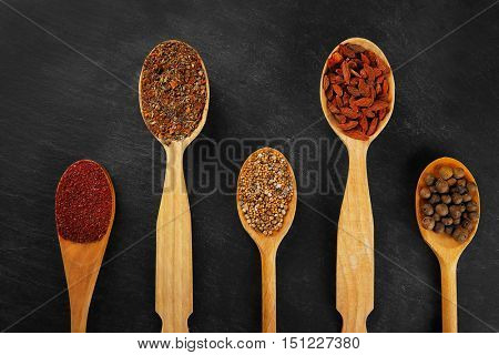 Spices in wooden spoons on a dark background