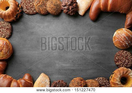 Frame of assorted fresh pastries on grey background