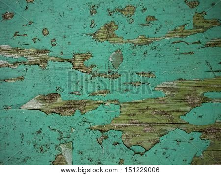 Grunge wood background with old green peeling paint, top view