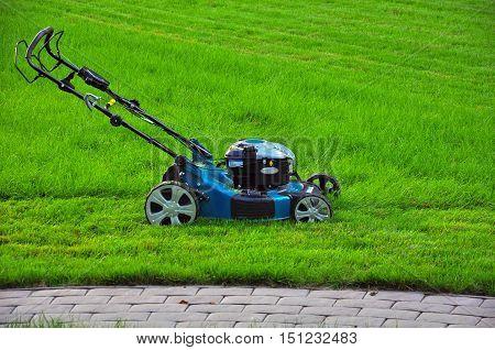 Lawn mower in the grait green grass