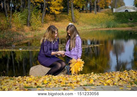 Mother and daughter walking in autumn Park