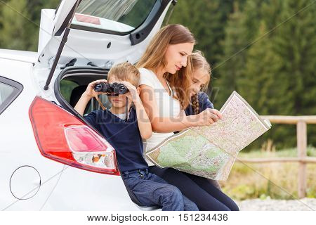 Family Travelling By Car And Using Map To Navigate