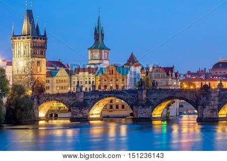 Famous Prague Landmarks - towers and bridge at night time with city illuminated, Prague, Czech, Europe