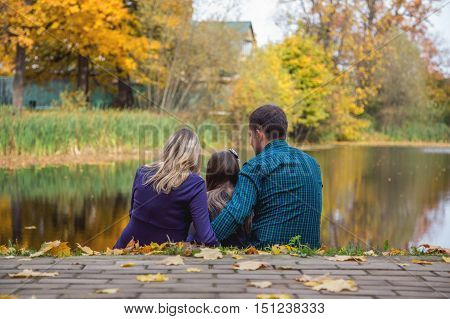 Happy family on the lake with his back turned