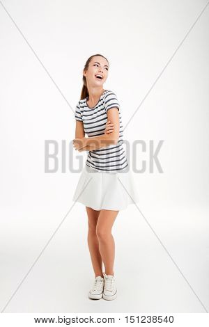 Full length portrait of a happy woman standing with arms folded isolated on a white background