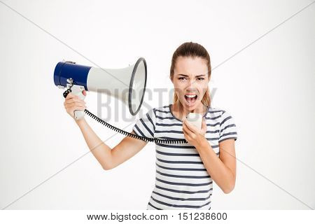 Young woman shouting into loudspeaker isolated on a white background