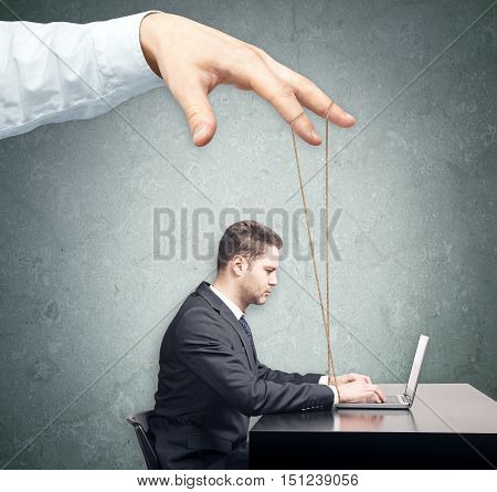 Hand controlling young businessman at workplace. Control concept