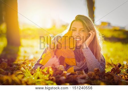 Happy young woman in park in autumn holding leaves and relaxing. Gorgeous cheerful girl lying on leaves outdoors, smiling, enjoying sunny fall day. Vibrant colors, back lit, natural lighting.