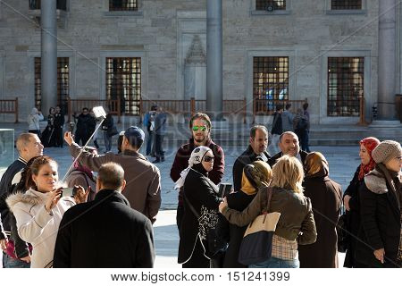 Multi national Group of People Men and Women from different Countries looking around taking self Portrait Photos stick for mobile Phone Tour at historical Spot. Istanbul, Turkey, November 18th, 2015