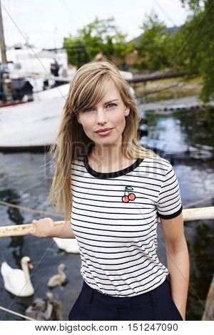 Blue eyed blond woman standing on habour in portrait