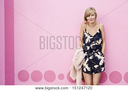 Beautiful blond woman in playsuit smiling pink wall