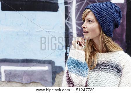 Cool girl in woolly hat looking away