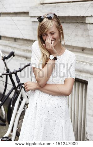 Giggling woman in white dress in the city