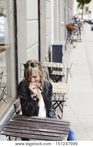 Giggling girl in cafe in city looking down