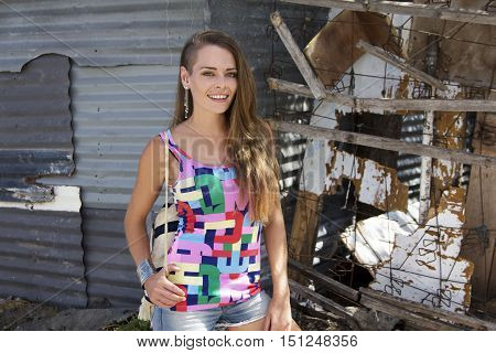 Caucasian female standing outside a corrugated shack wall and homemade fence in a township in Africa