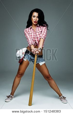 Full length portrait of young woman in jeans shorts, red checked shirt, red lips with bat