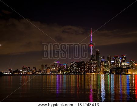 City skyline at night with colourful lights reflecting on a lake.