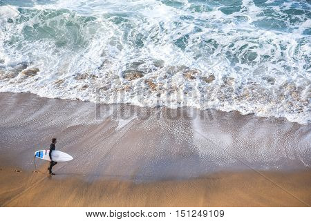 surfer man on the beach with turquoise-white water wave in the sea from top view at Bells beach Torquay Australia