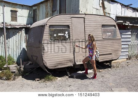 Female checking if anyone is home in an old beaten up caravan in an African township
