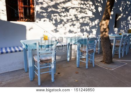 Restaurant tables under a tree with small bottles of olive oil.