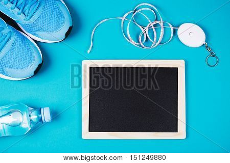 Fitness background made of sneakers, bottled water, measuring tape and clean chalkboard on blue background. Concept of healthy lifestile, everyday training and force of will. Flat lay style of picture
