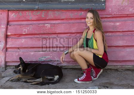 Caucasian female outside of a shack with a stray dog in an African township