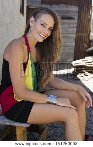 Caucasian female sitting outside of a shack in an African township smiling