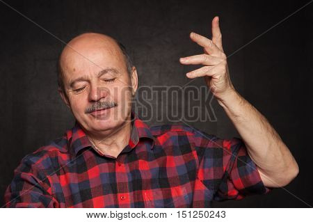 elderly man in a plaid shirt playing the fool and ape