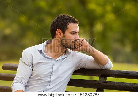 Depressed businessman is sitting at the park and thinking about something.