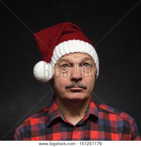 Bad mood before Christmas. Man in New Year's cap looks sad.