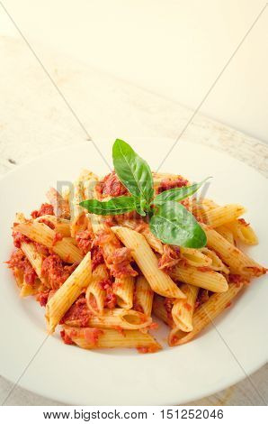 Italian Wholemeal Pasta Penne with Tuna and Basil. Fresh pasta with tuna and tomato sauce on white wooden background with place for text. Italian cuisine concept. Copy space. Selective focus.