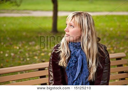 Young Woman Sitting On Bench At Autumn Park.