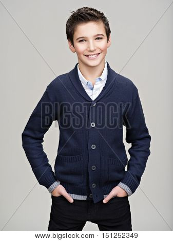 Happy pretty teenage boy posing at studio as a fashion model.