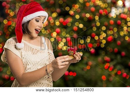 Christmas Gift - Woman Opening Gift Surprised And Happy, Young Beautiful Smiling Woman In Santa Hat.
